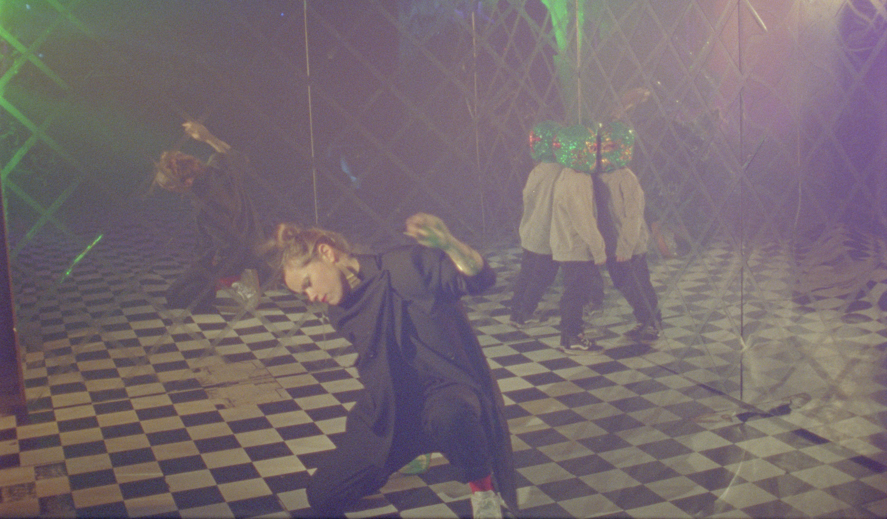 Interior shot of a nightclub with black and white floor, and mirrored walls. A white-skinned woman with blonde hair tied up in a messy top-knot appears to breakdance on the floor. She is wearing a draped black two-piece, red socks and white sneakers. She wears red lipstick and metal jewellry. In the rear of the room, a small child pushes his whole body up against the mirror wall. He is wearing an oversize green sequined Lucha libre mask, a grey sweater, black trousers and dark sneakers. A disco ball refracts blue, purple and green light all over the dancefloor.