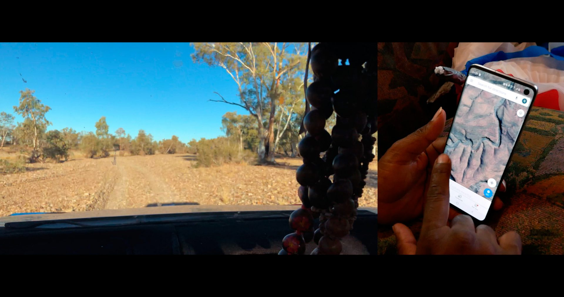 A horizontal image and a vertical image are laid out together. On the left, the horizontal image depicts an arid desert landscape from the perspective of a car dash. In the foreground, chunky beads hang from the rearview mirror. In the background are dry mud flats, scrub trees and bushes, and cloudless blue sky. On the right portrait-oriented image, a brown-skinned left hand holds out a smartphone and the right-hand index finger points at an image on the smartphone screen. The smartphone screen depicts a topographical satellite image of a dry landscape with a water-less river bed.